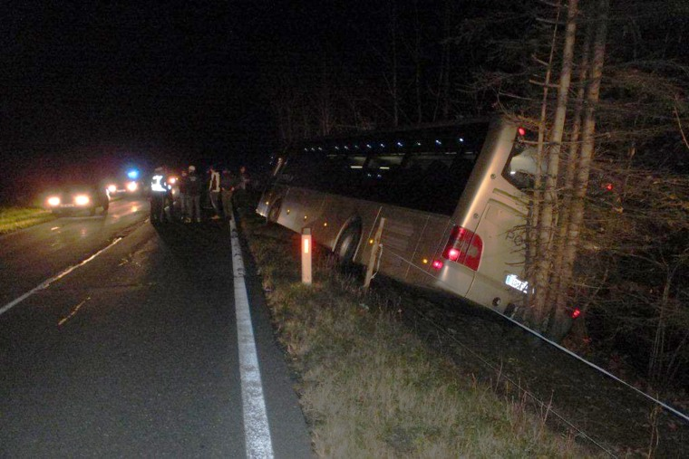 Image: A bus sits in a ditch on the side of the road