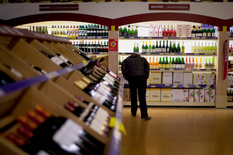 Image: a Chinese man checks out the imported wine in a supermarket in Beijing