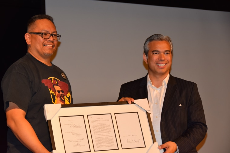 Johnny Itliong receives a copy of the bill that made Oct. 25 Larry Itliong Day annually in California from Assemblyman Rob Bonta.