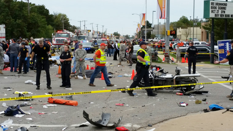 Image: Emergency personnel respond after a vehicle crashed into a crowd of spectators