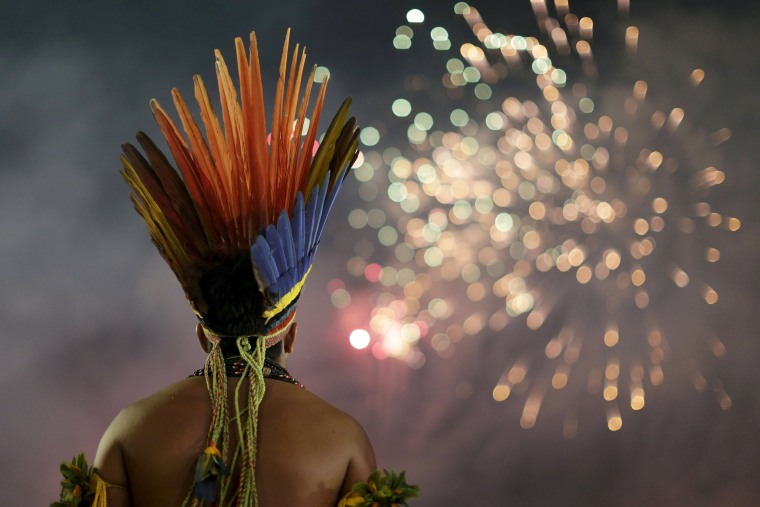 Image: An indigenous man watches fireworks during the first World Games for Indigenous Peoples in Palmas