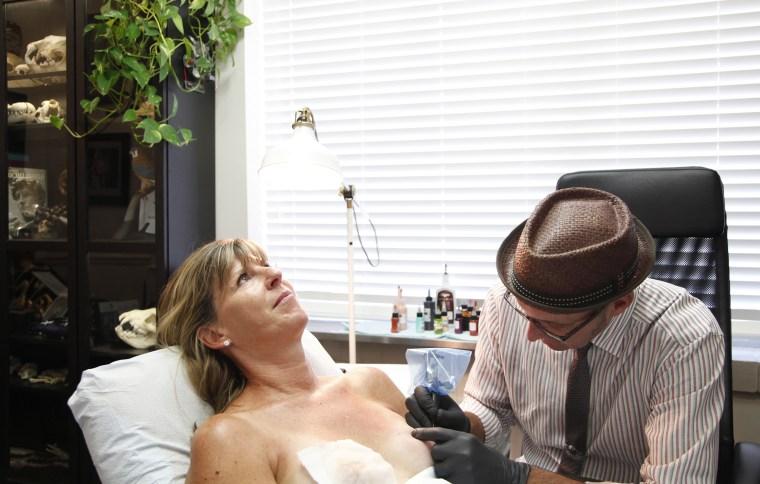 Nipple tattoo artist Vinnie Myers works on client