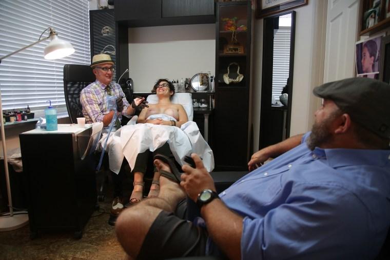Nipple tattoo artist Vinnie Myers works on a client