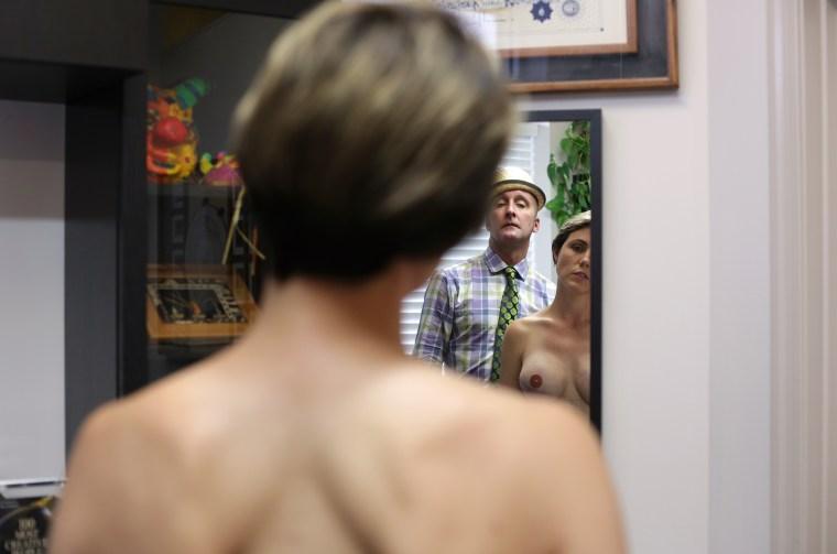 Nipple tattoo artist Vinnie Myers examines a breast cancer survivor