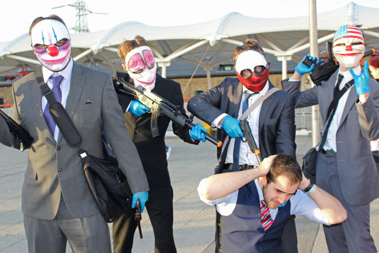 "A kneeling man pretends to be a bank manager as he's surrounded by attendees dressed as characters from the video game ""Payday"" at MCM Comic Con in London. The event required attendees to place orange or red caps on the muzzle of plastic pistols and rifles."