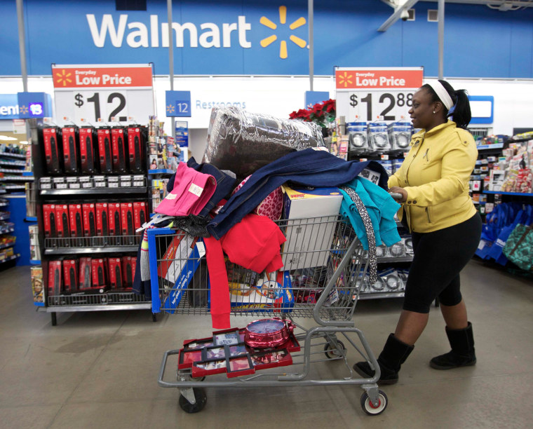 Image: A woman with a full shopping cart heads to the checkout at a Wal-Mart Store in Chicago