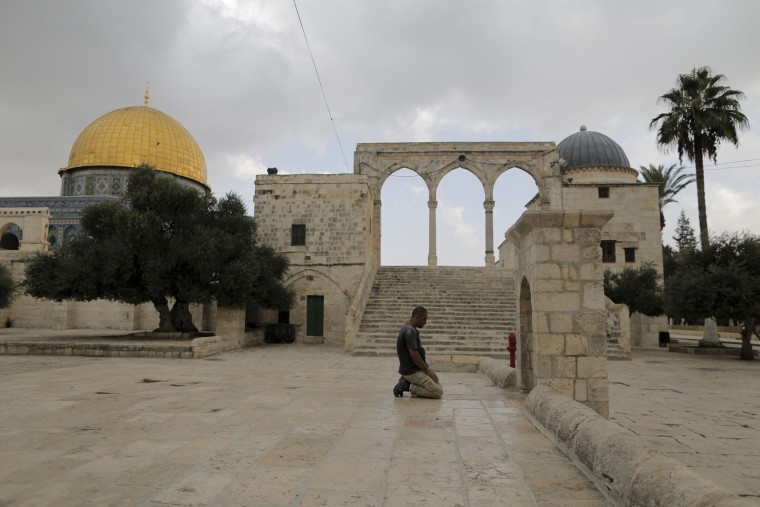 Image: A Muslim man prays near the Dome of the Rock  in Jerusalem