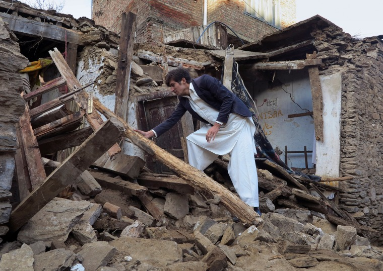 IMAGE: A boy examines a house damaged by massive earthquake