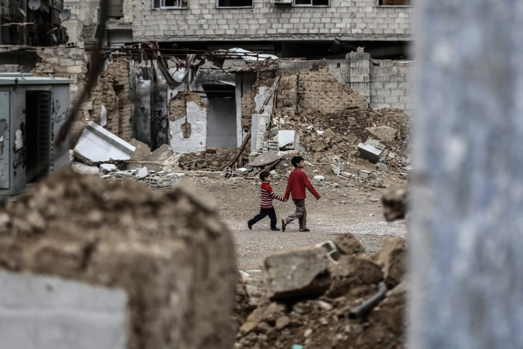 Image: Two Syrian boys walk past destroyed houses