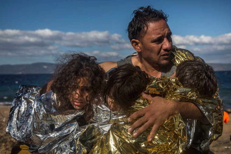 Image: A man holds three children wearing thermal blankets