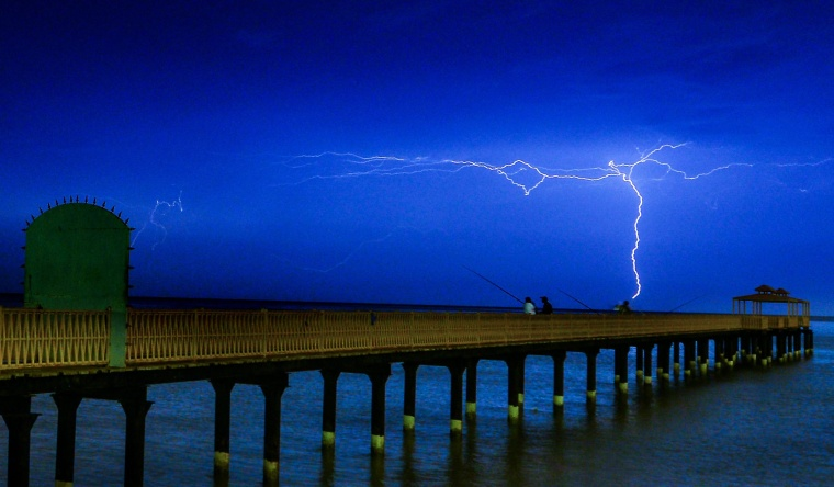 Lightning flashes over people fishing on the coast near Kuwait City, Kuwait.