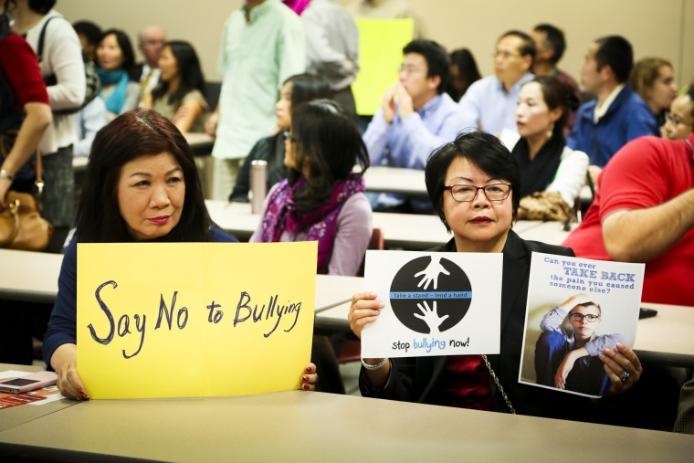 Louisa Luk and Gail Young hold signs against bullying during the Fairfield School Board meeting Thursday, Oct. 15, 2015, in Fairfield, Ohio. A large crowd was present to protest the ongoing bullying at Fairfield Middle School and the lack of action by administrators.