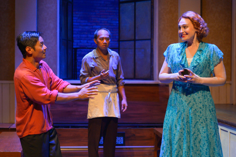 """Vicente Pacram (Ogie Zulueta, left) serves a Filipino dish to Althea Benton (Kelsey Venter) in his room at the I-Hotel while Fortunado """"Nado"""" Giron (Jomar Tagatac, center) looks on in """"Remember the I-Hotel,"""" a one-act play by Philip Kan Gotanda adapted from """"Monstress,"""" Lysley Tenorio's book of short stories."""