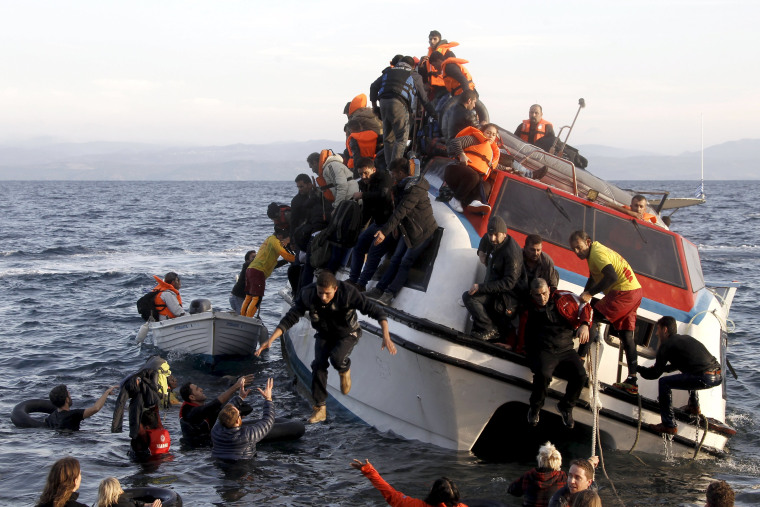 Image: Refugees, most of them Syrians, on a half-sunken catamaran nearing the Greek island of Lesbos.