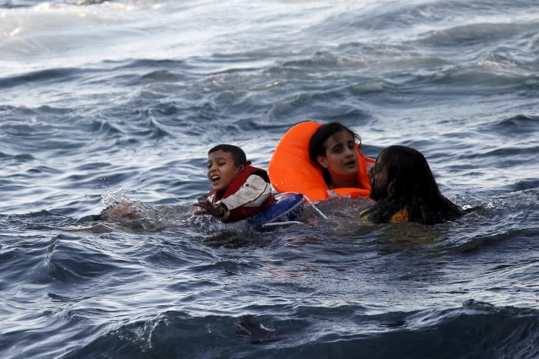 Image: A boy cries out for help as a half-sunken catamaran arrives off the Greek island of Lesbos on Friday.
