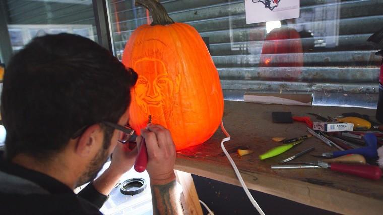An artist at Maniac Pumpkin Carvers works on a pumpkin.