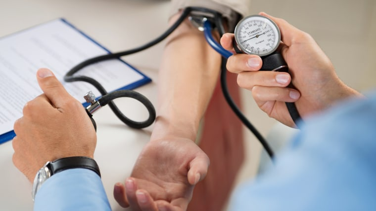 Image: Doctor checks a patient's blood pressure