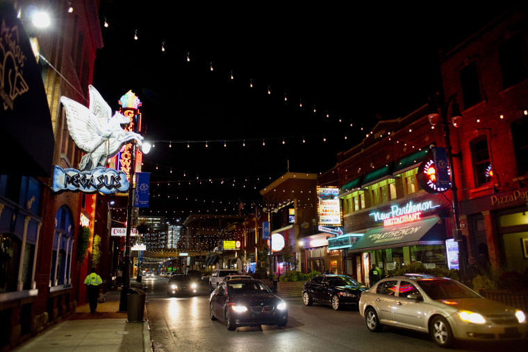 Lights are strung across the street at night as cars move along Monroe Avenue in the Greektown neighborhood of downtown Detroit, Michigan, U.S., on Tuesday, Oct. 13, 2015. Ten months after emerging from a record $18 billion municipal bankruptcy, Detroit is functioning in ways unseen for months and even years -- street lights are on, parks get mowed, municipal debt is sold on the public market and the police are training civilians to manage traffic at clogged intersections.