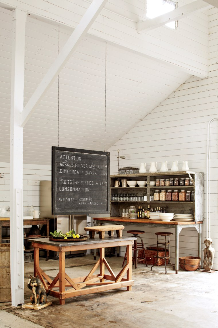 Here a vintage industrial kitchen rack with butcher-block top stores a selection of antique ironstone dishes and pitchers. The nineteenth-century bluestone table and a vintage American chalkboard made for the perfect prep area while entertaining.
