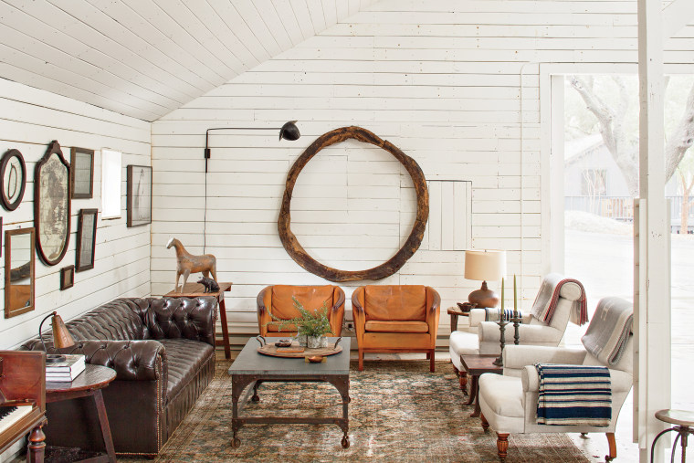 We used this barn like a dining room and kitchen. This seating area is made up of Danish leather armchairs, a bluestone coffee cocktail table, a pair of antique armchairs in Belgian linen, and a vintage leather chesterfield. On the floor is a nineteenth century tribal carpet, and on the wall hangs an eighteenth-century Spanish wood ring.