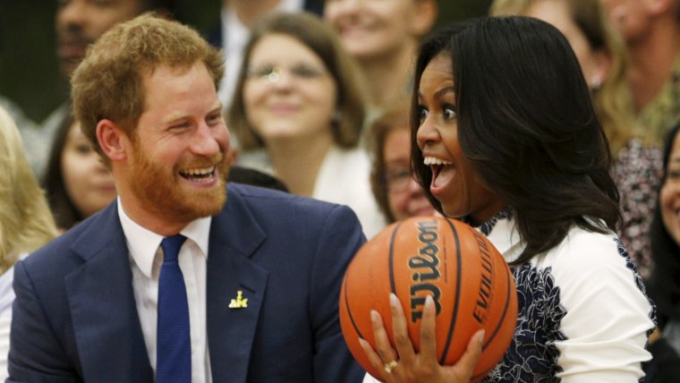 Image: Britain's Prince Harry hands U.S. first lady Michelle Obama the basketball at the end of a game played by wounded warriors at Fort Belvoir, Virginia