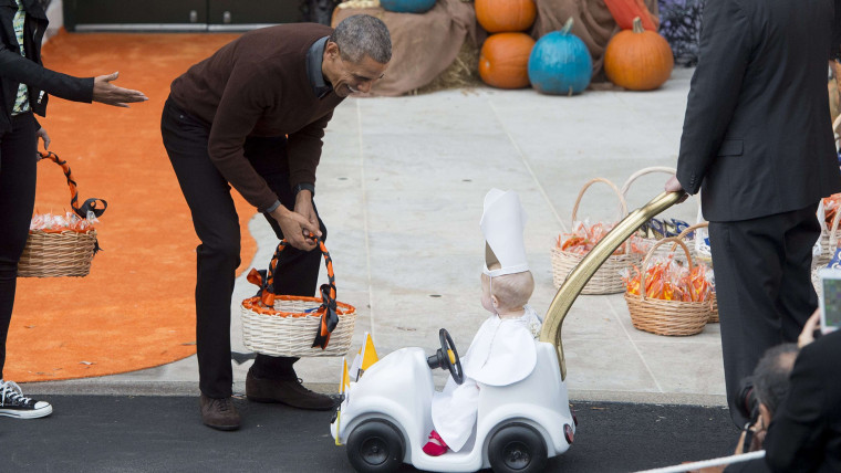 Obama greets a young child dressed as the Pope