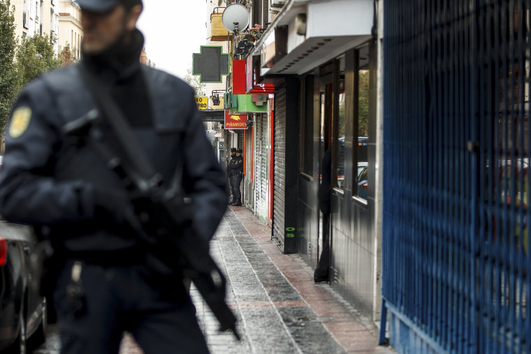 Image: Spanish police stand guard as they search the home in Madrid