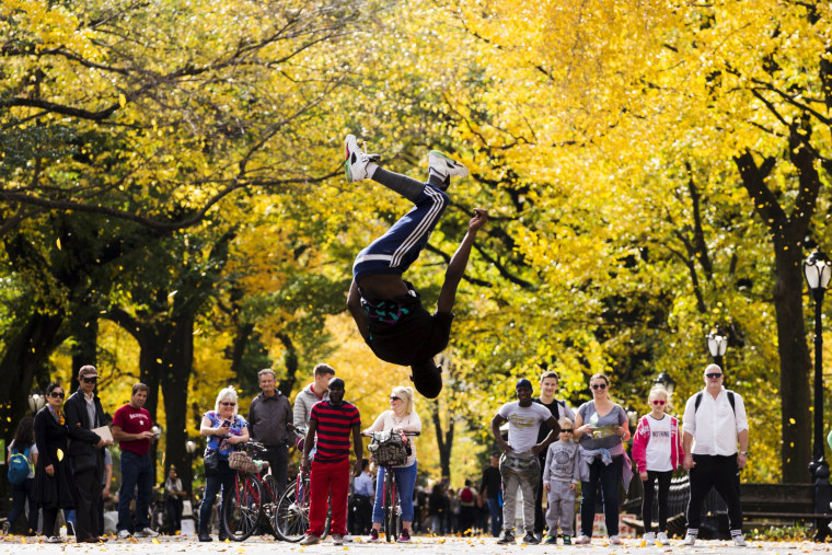 Image: A street performer jumps in the air