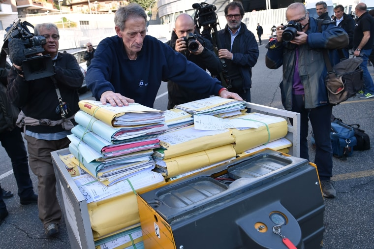 Image: An official pushes a cart with legal files into Rome's criminal court