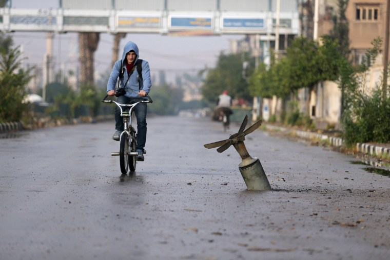Image: A resident rides his bicycle near what activists said was an  exploded cluster bomb shell in the town of Douma, eastern Ghouta in Damascus