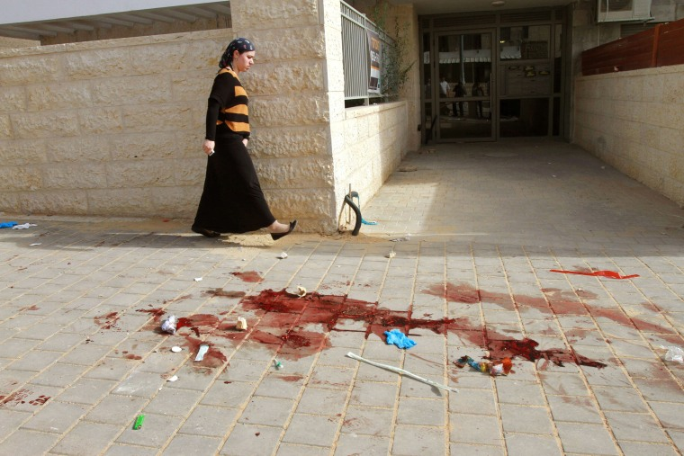 Image: A woman walks past a pool of blood where earlier two alleged Palestinian attackers