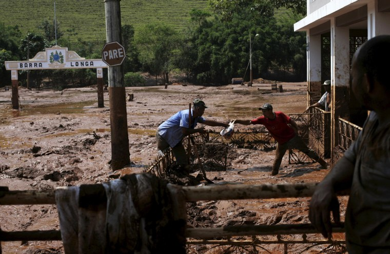 Image: Men take out a bag from a house flooded with mud after a dam owned by Vale SA and BHP Billiton Ltd burst, in Barra Longa