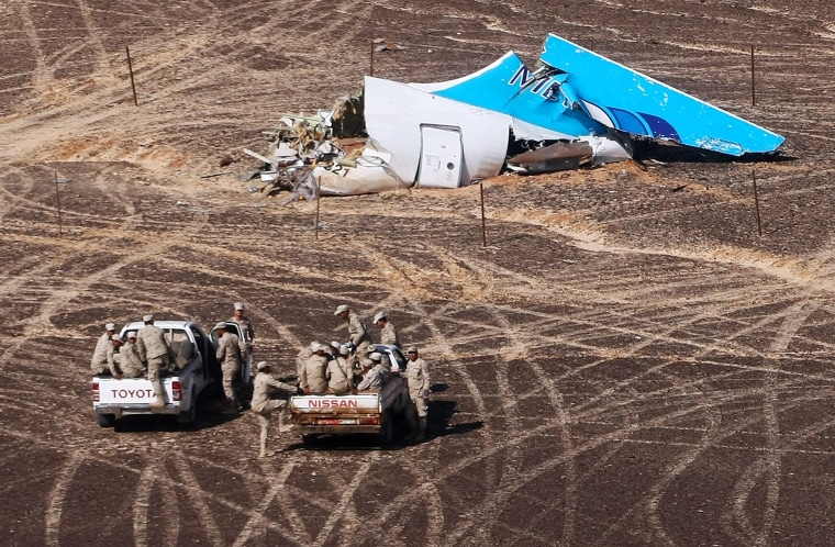 Image: Egyptian Military approach a plane's tail at the wreckage