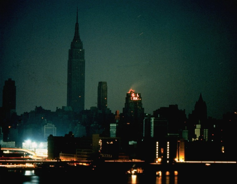 Image: The usually bright New York skyline stands in darkness with only a few generator powered buildings illuminated.