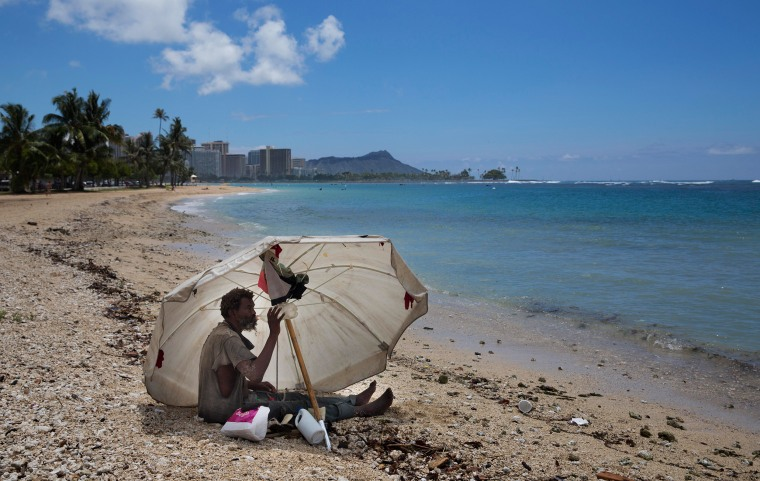 Image: A homeless man drinks water while sitting on the beach at Ala Moana Beach Park