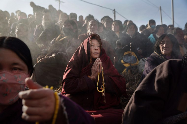 Image: A Tibetan Buddhist monk prays with laypeople
