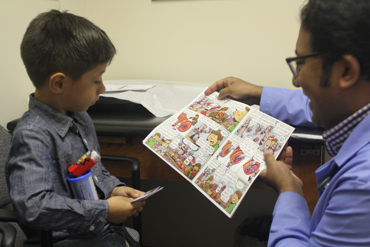 """Dr. Alex Thomas shows an """"Iggy and the Inhalers"""" comic to a young patient."""