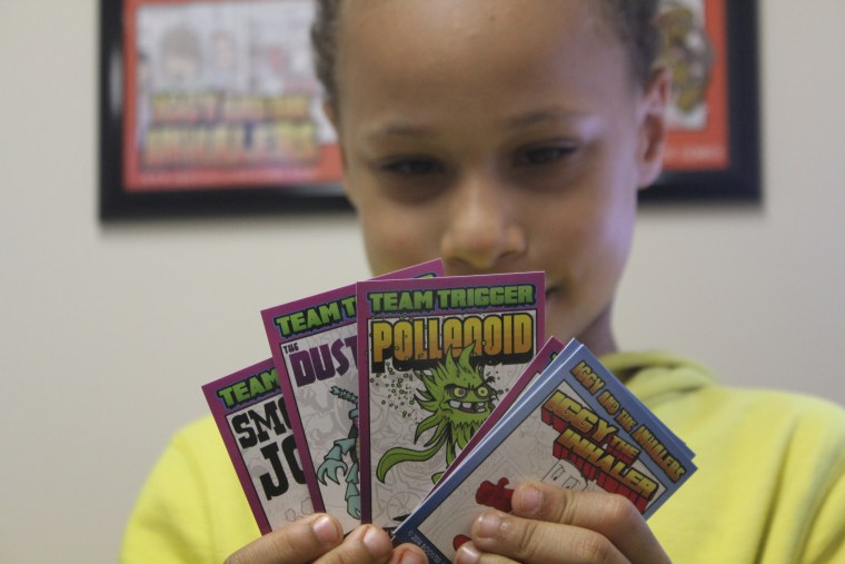 """A young patient holds """"Iggy and the Inhalers"""" trading cards."""