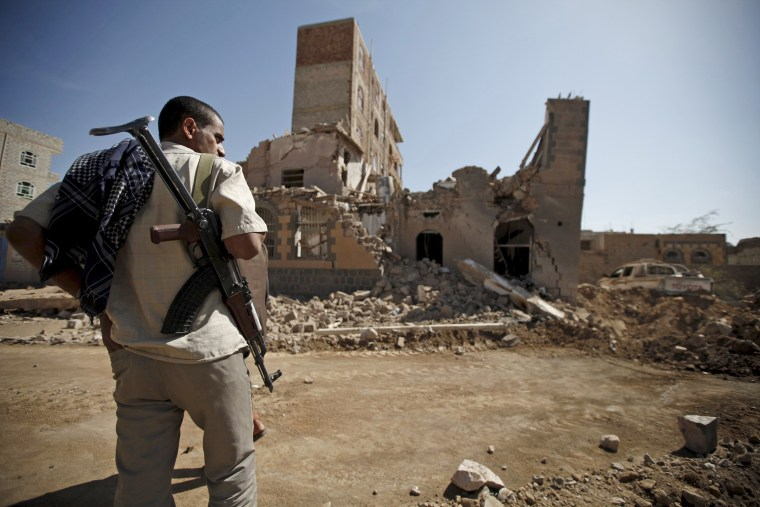 Image: Houthi militant stands past a destroyed house at the site of Saudi-led air strikes in Yemen's capital Sanaa