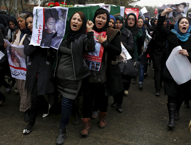 Image: Women chat slogans as they carry one of the coffins
