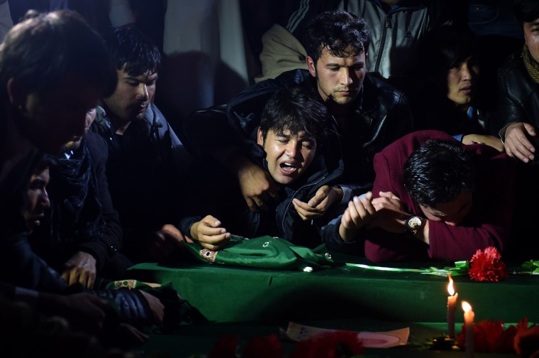 Image: Men mourn over the coffins
