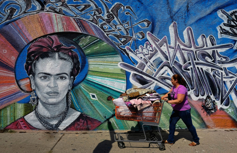 Image: A woman pushes a shopping cart past a mural of late Mexican painter, Frida Kahlo