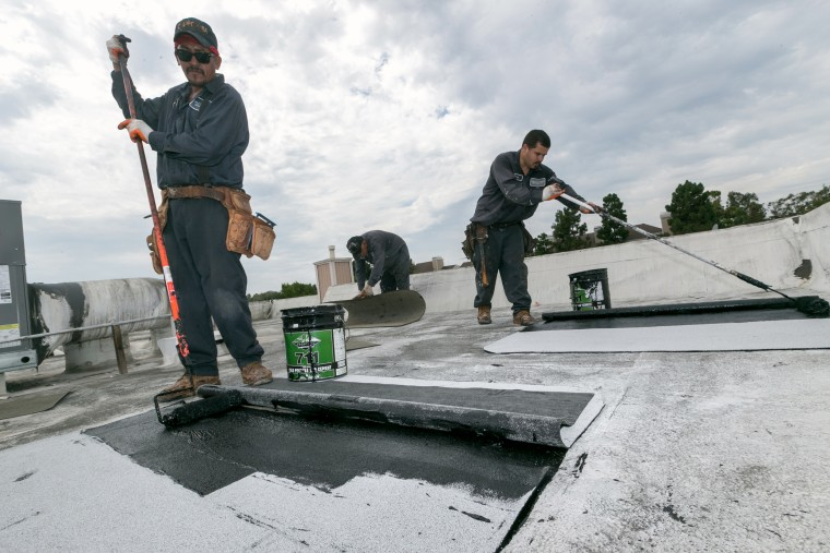 Image: Roofers Javier Rubio, left, and Joel Camberos
