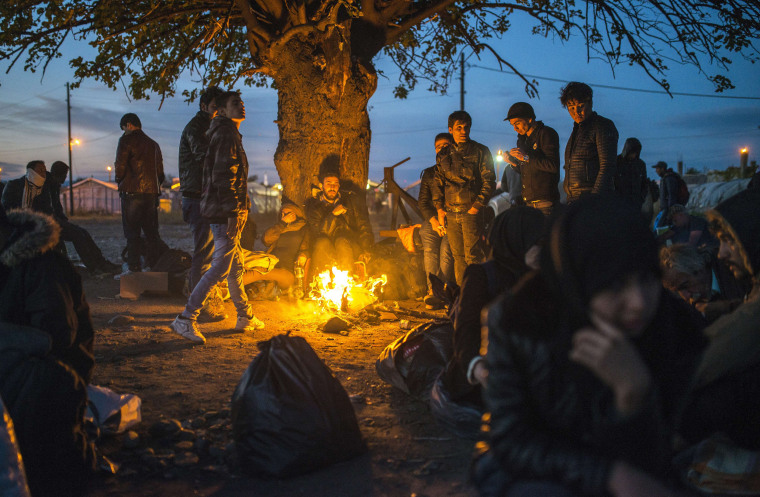 Image: Migrants and refugees keep warm around a bonfire
