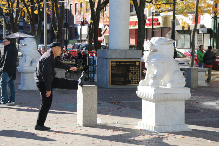 An old man stretches in front of the Chinatown Gate of Boston.