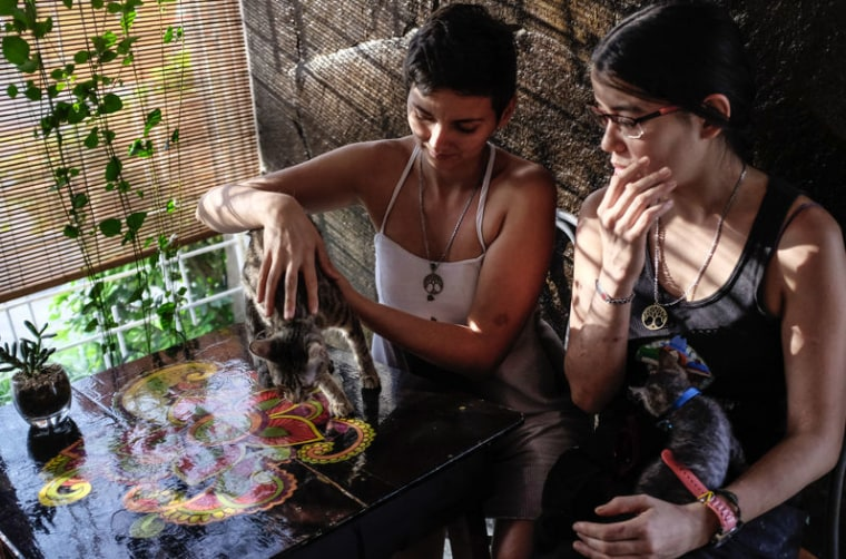 In this Nov. 3, 2015 photo released by La Nación, Jazmin Elizondo Arias, left, sits with her partner Laura Florez-Estrada Pimentel with their two recently adopted kittens, at a restaurant in San Jose, Costa Rica.