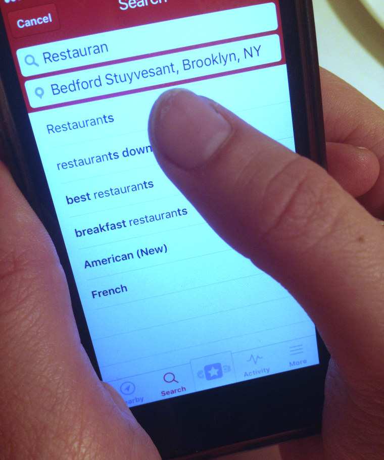 Photo: A smartphone user reads a Yelp review.
