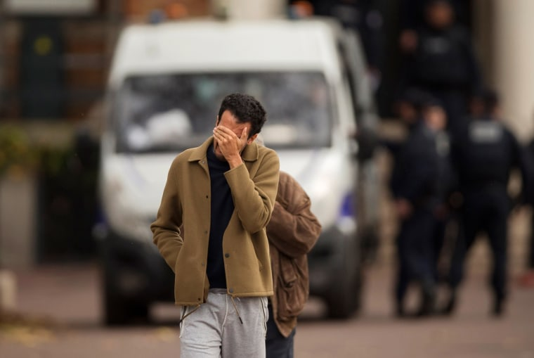Image: A man hides his face as he leaves the morgue in Paris