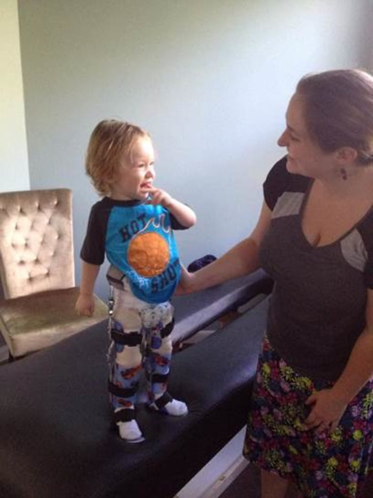 Kaden Myers tries out his new leg braces with his mom, Katie Myers.