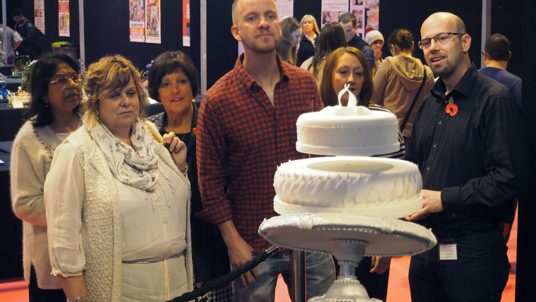 People confused by the cake at the Cake International Show.
